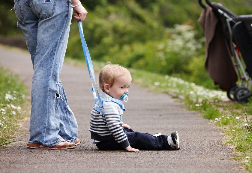 Erwachsene Person hält ein am Boden sitzendes Kind an einem Laufgurt