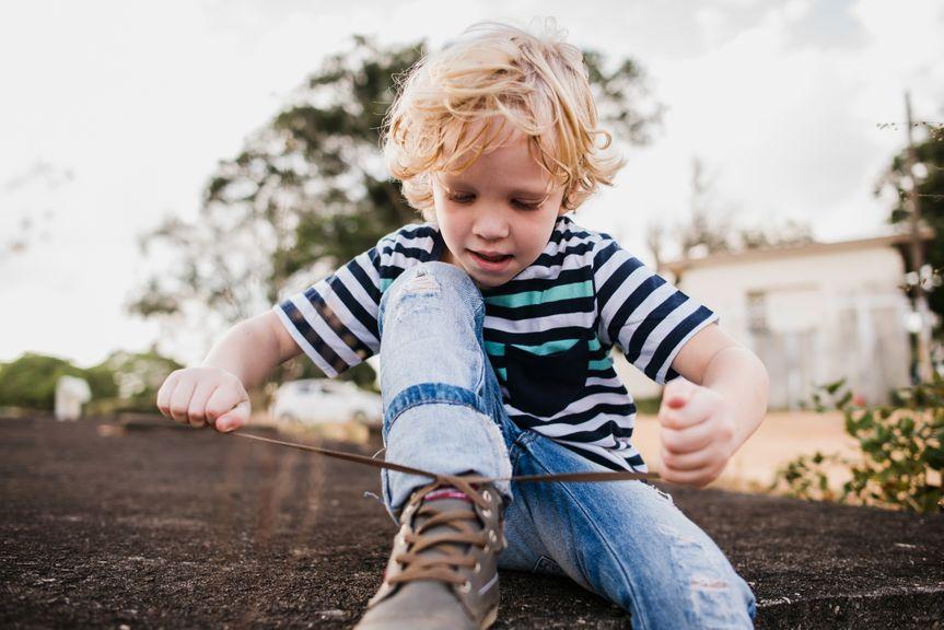 Kind bindet den Schuh