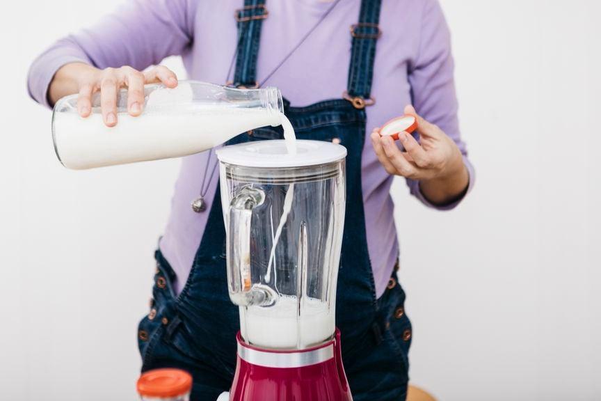 Schwangere giesst Milch in den Mixer für Smoothie