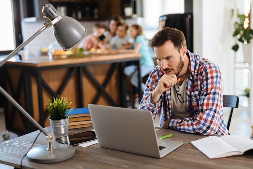 Mann macht Büroarbeiten, Familie im Hintergrund