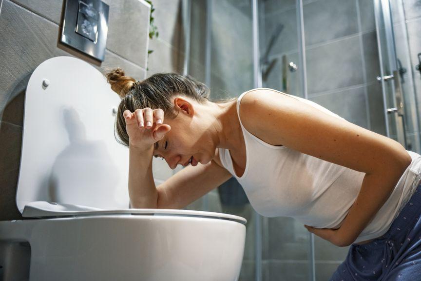 Frau mit Brechreiz beugt sich über das WC