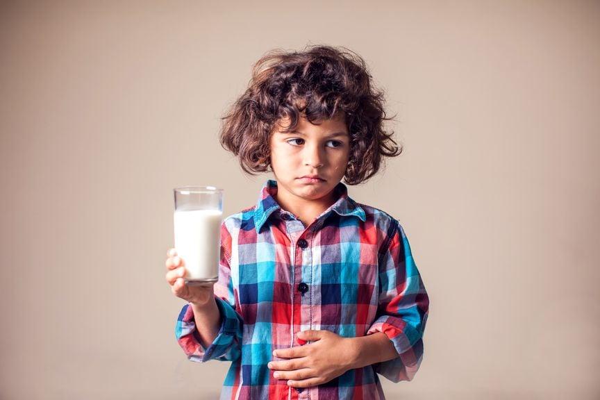 Junge mit einem Glas Milch in der Hand hat Bauchschmerzen