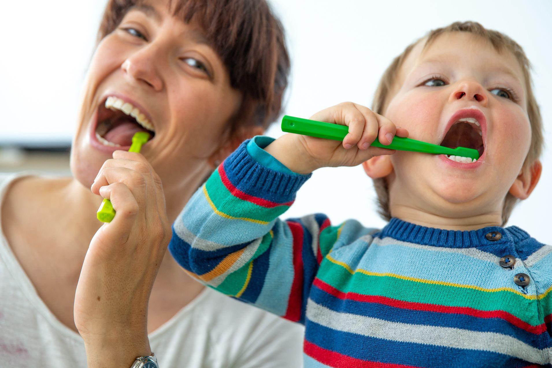 Mutter und Kind putzen sich die Zähne