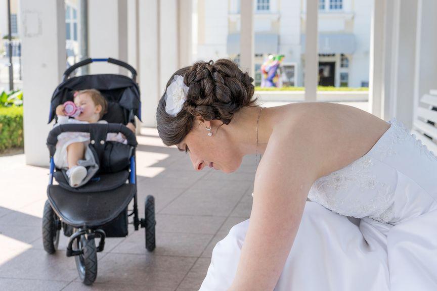 Mutter im Hochzeitskleid, Baby im Kinderwagen