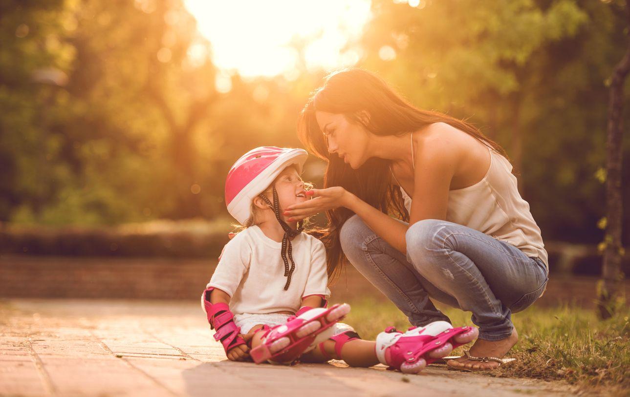 Mutter tröstet Kind nach Sturz
