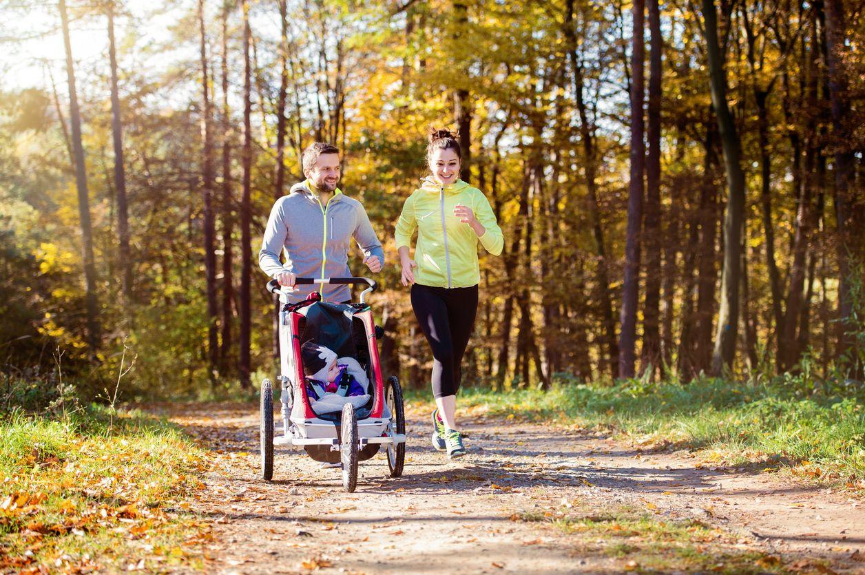 Eltern beim Joggen mit Buggy am Waldrand