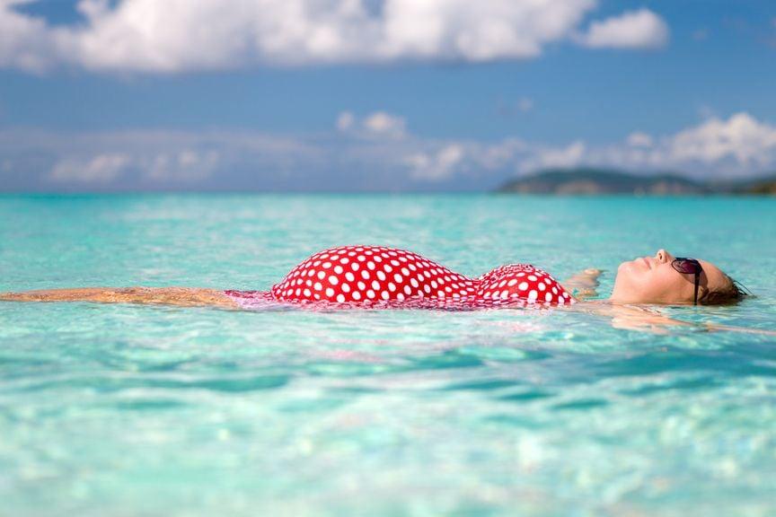 Schwangere lässt sich im Meerwasser treiben