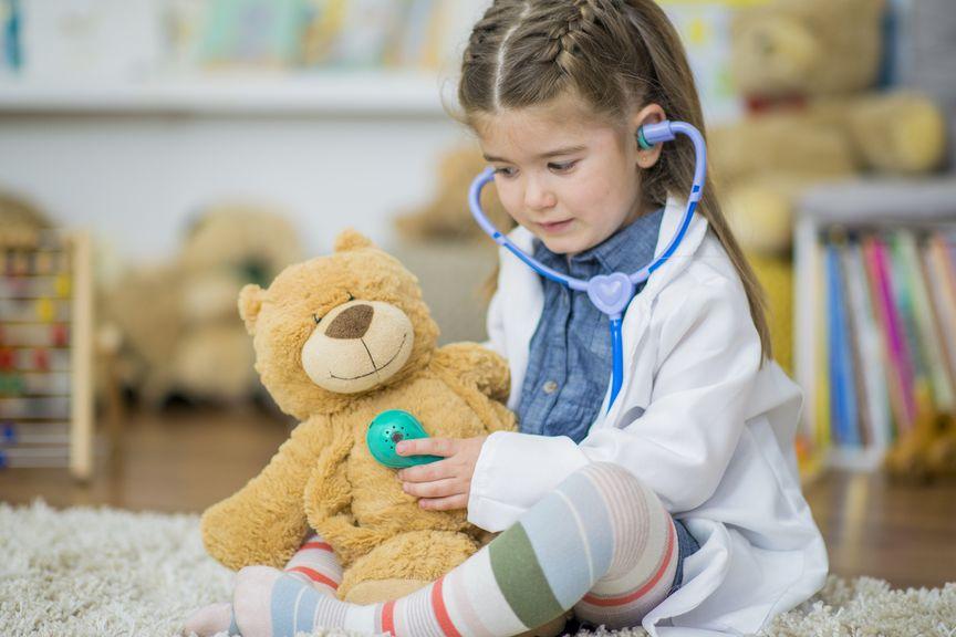 Mädchen spielt Kinderarzt; Herzabhören beim Teddy