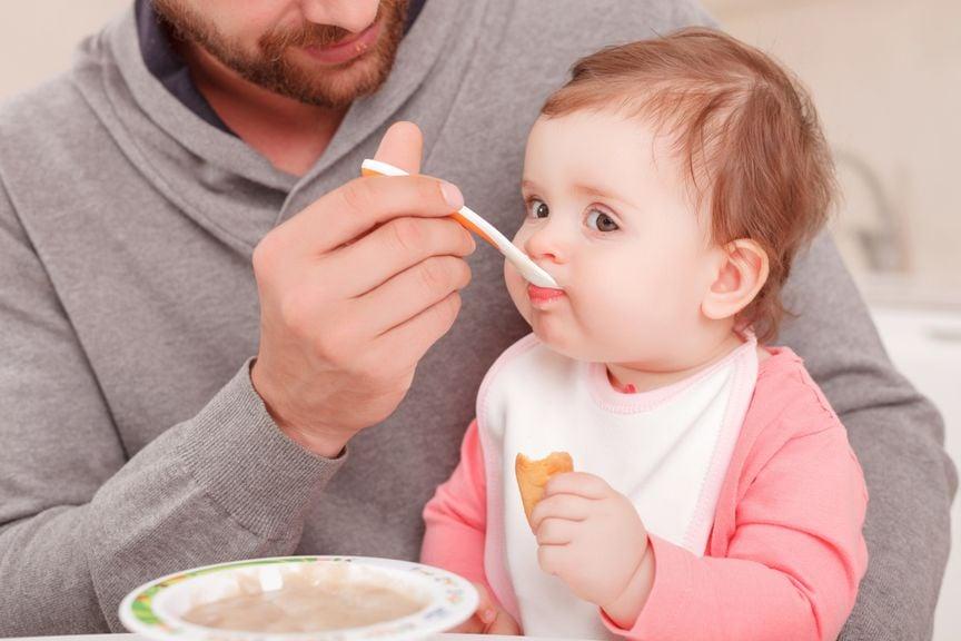Vater füttert seine kleine Tochter