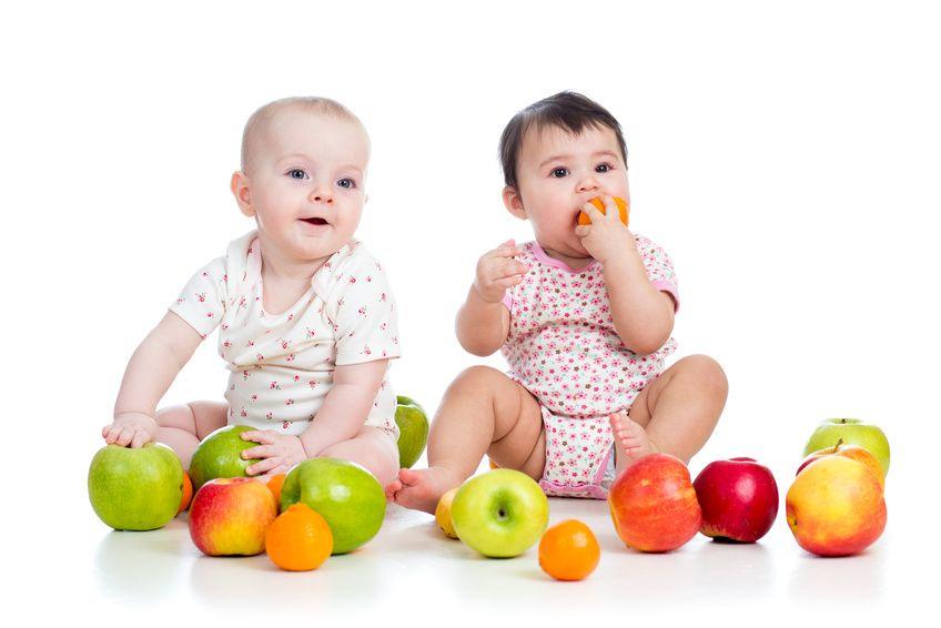 zwei Babys mit diversen Früchten
