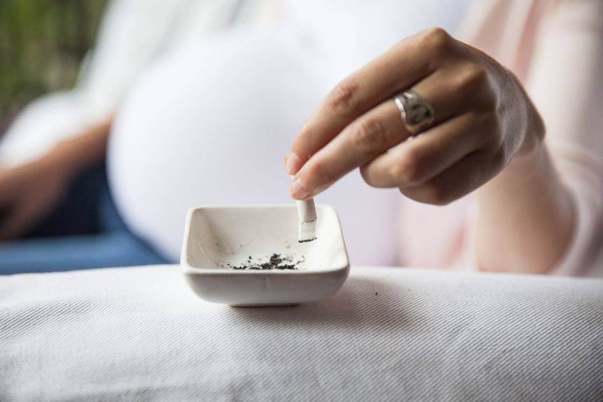 Schwangere drückt Zigarette aus