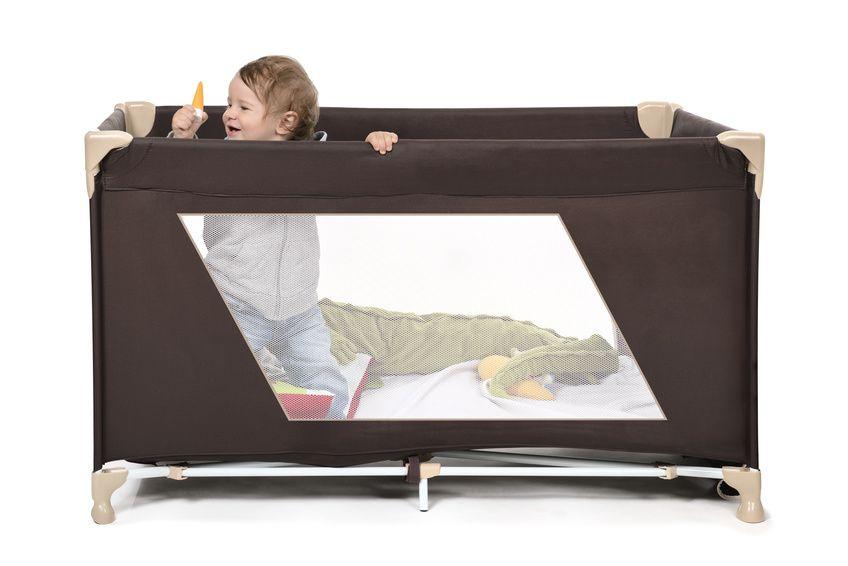 Baby steht im Kinderreisebett