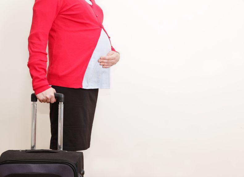 Schwangere mit Rollkoffer
