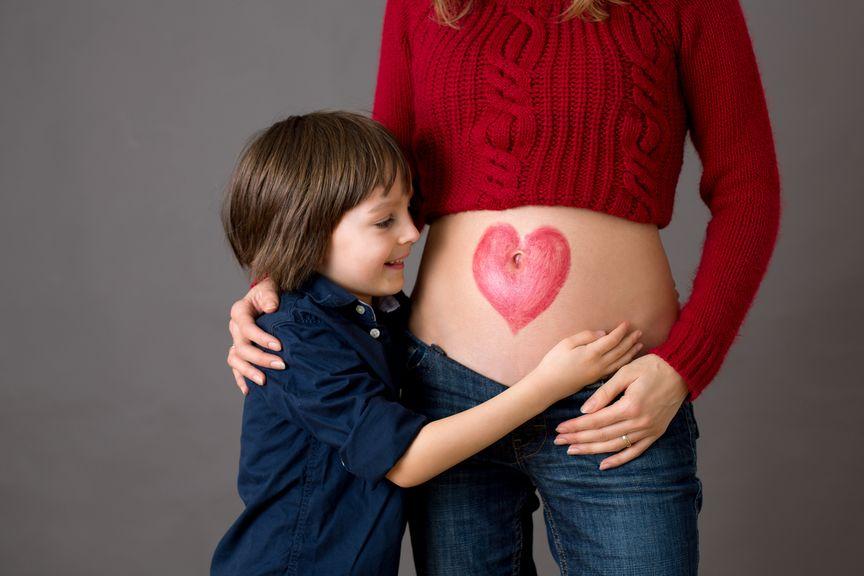 Geschwister umarmt den dicken Bauch mit aufgemaltem Herz