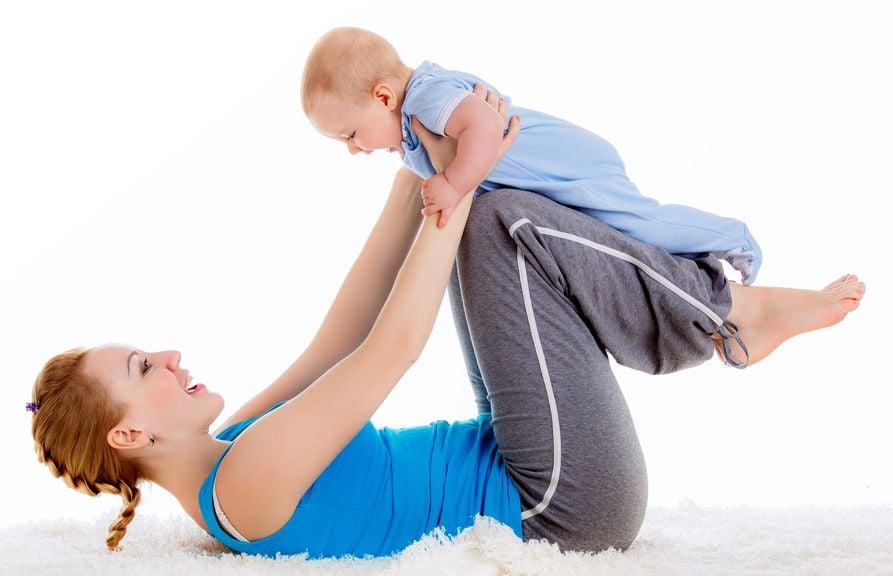 Mutter stemmt Baby mit den Beinen hoch