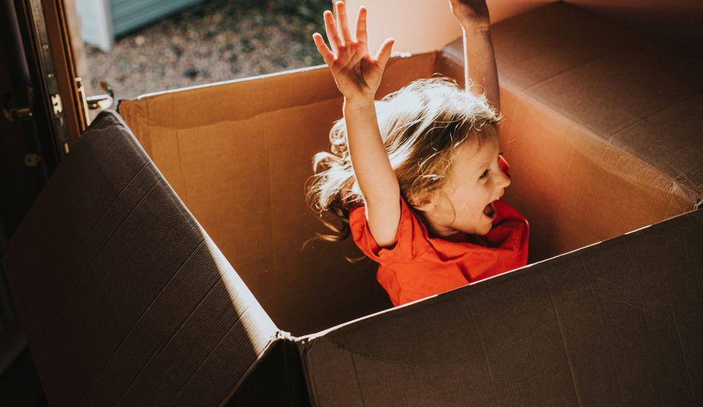 Kind spielt in einer grossen Kartonschachtel