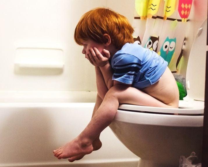 Kind sitzt auf dem WC