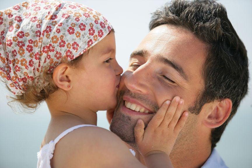 Mädchen küsst Vater auf die Backe