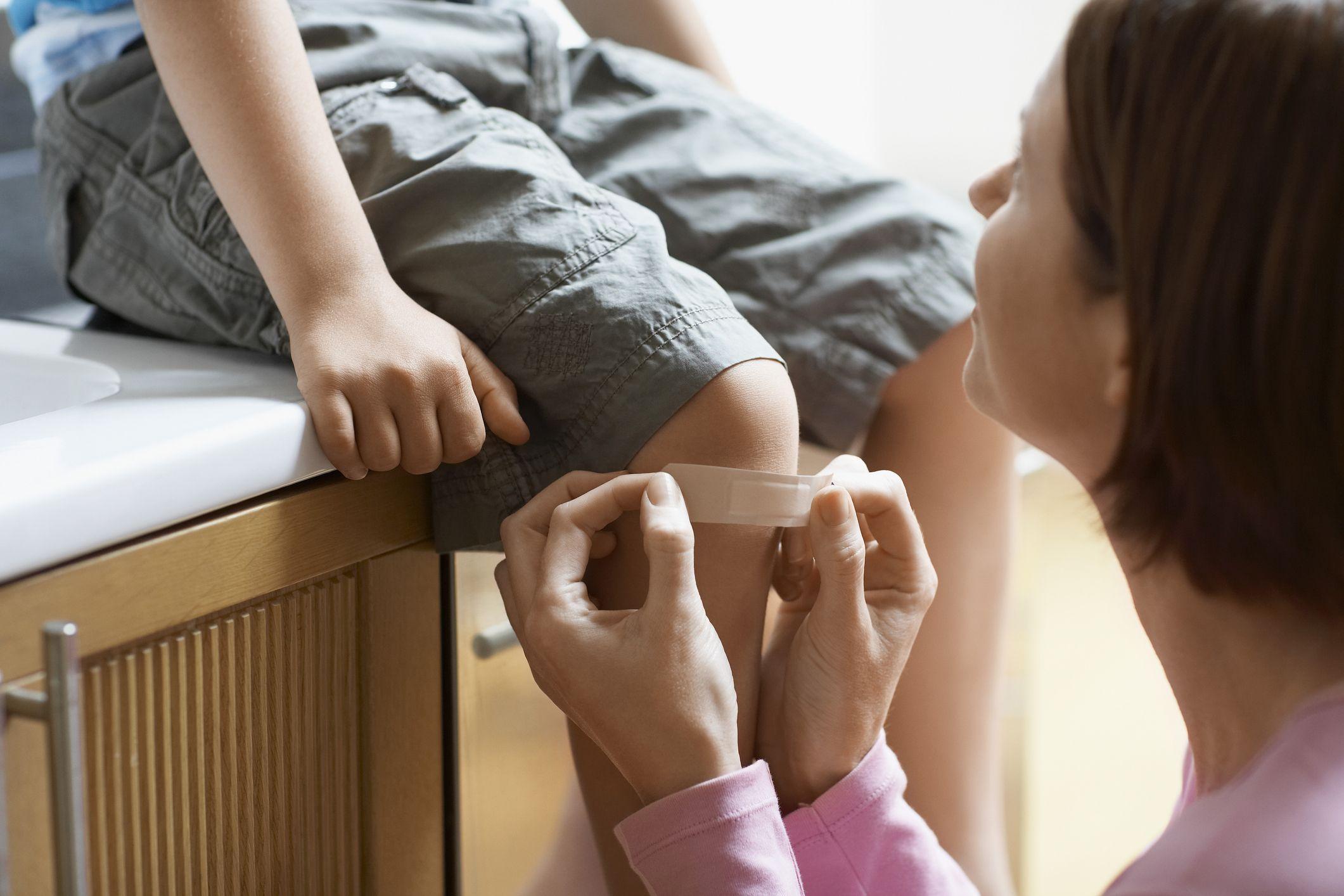 Mutter klebt ein Pflaster auf ein verletztes Knie eines Kindes