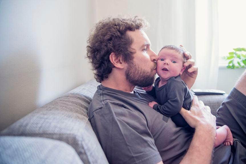 Vater küsst sein Baby auf die Backe