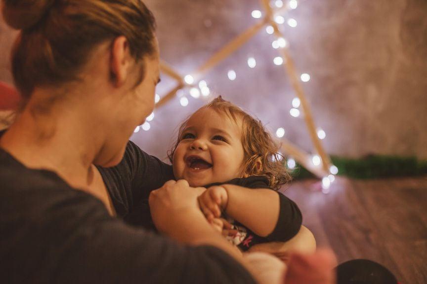 Mutter und Kind fröhlich bei Weihnachtsbeleuchtung
