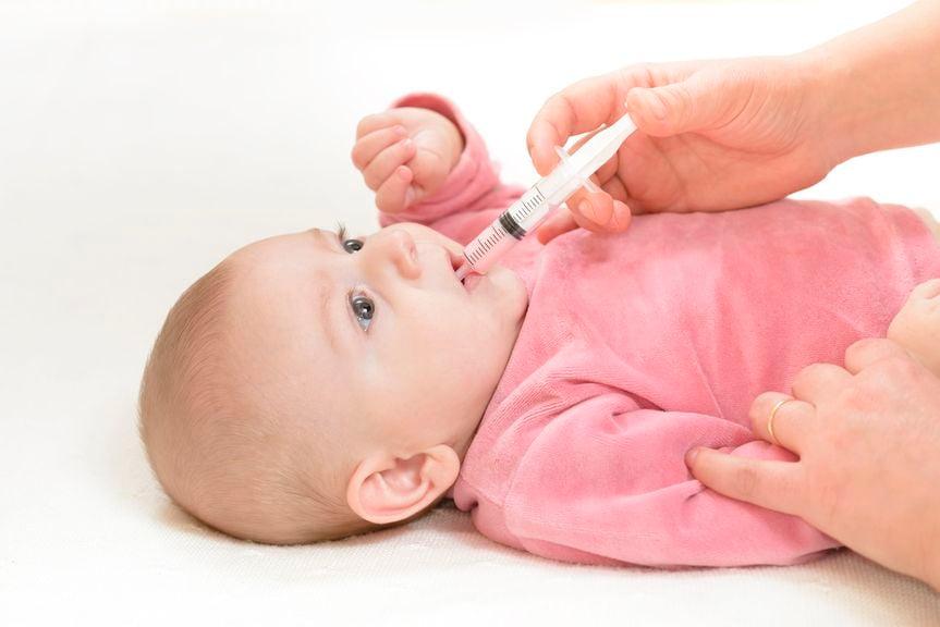 Baby bekommt ein Medikament mit einer Spritze in den Mund