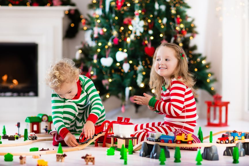 Geschwister mit Holzeisenbahn vor dem Weihnachtsbaum