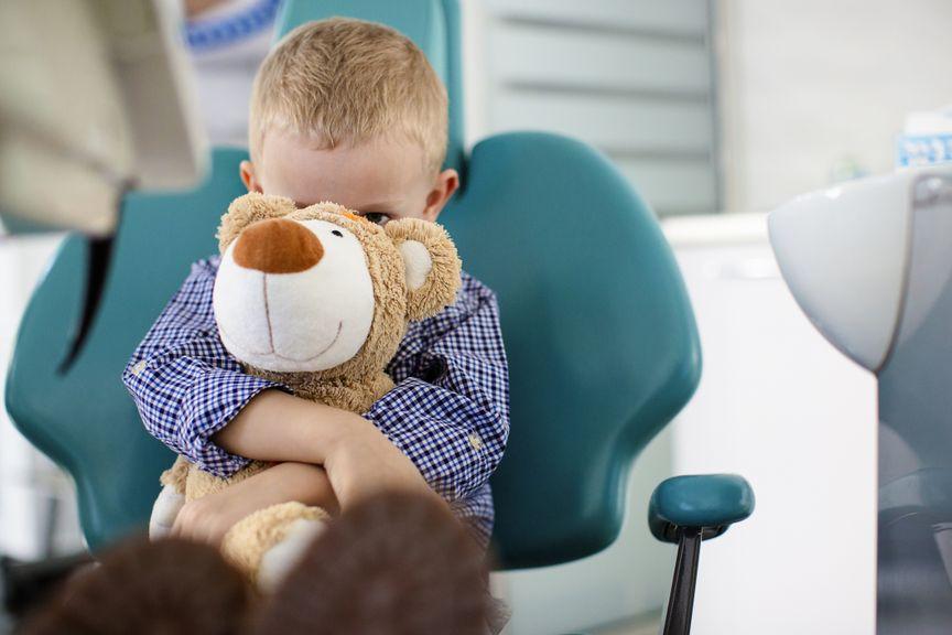 Ängstlicher Junge mit Kuscheltier auf dem Zahnarztstuhl