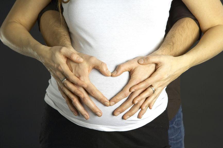 Schwangere mit Mann, der ihren Babybauch hält