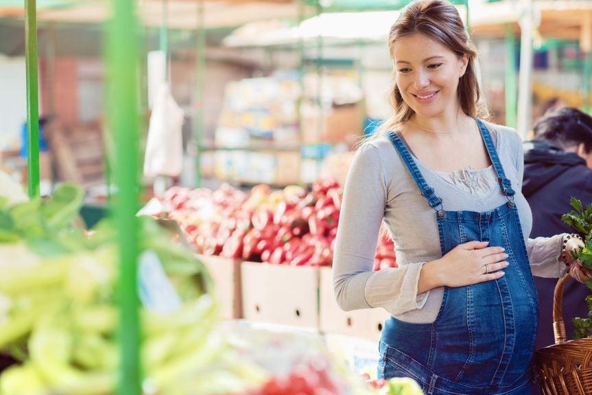 Schwangere im Jeansoverall kauft ein in der Gemüseabteilung