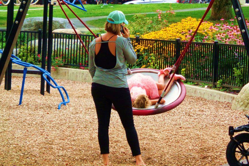 Mutter mit Natel auf dem Spielplatz
