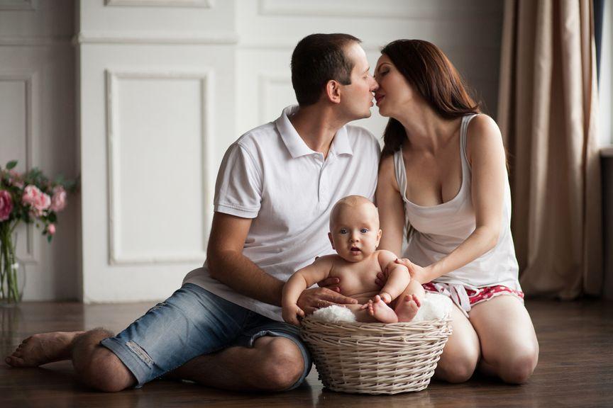 Paar mit Baby küsst sich