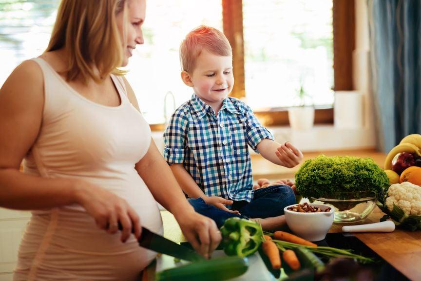Schwangere und Sohn beim Kochen