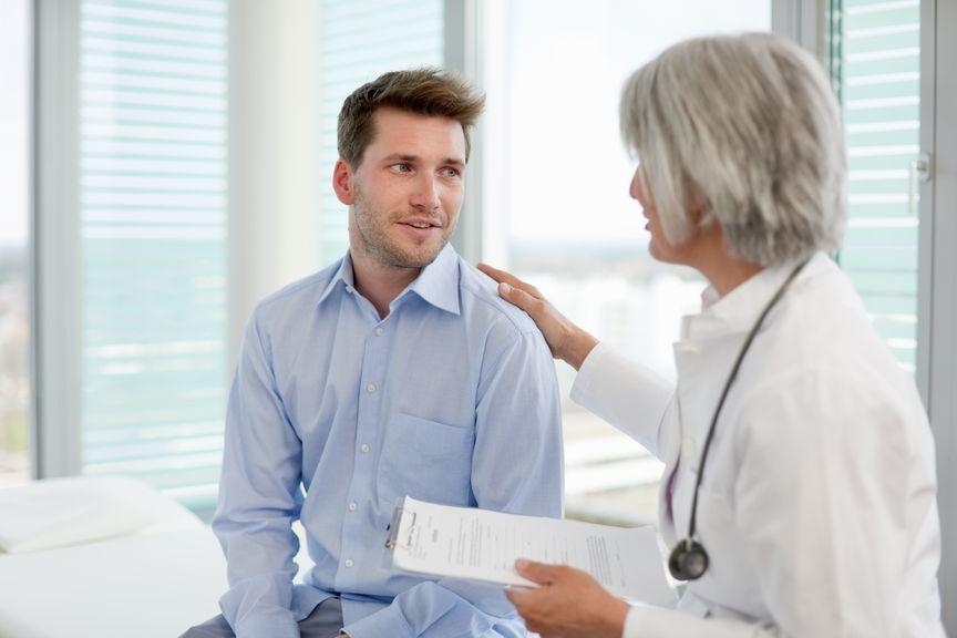 Mann in einer Arztpraxis spricht mit der Ärztin