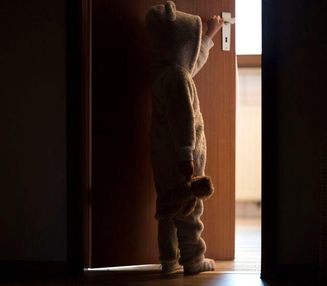 Kind im Plüschpyjama öffnet die Zimmertür
