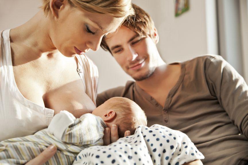 Mutter stillt ihr Baby, Vater schaut zu