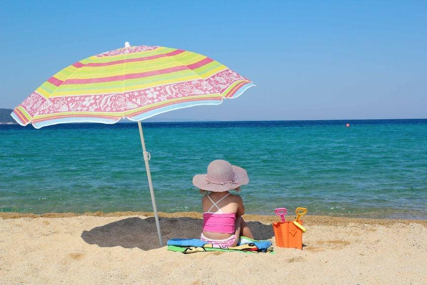 Kind am Strand unter dem Sonnenschirm