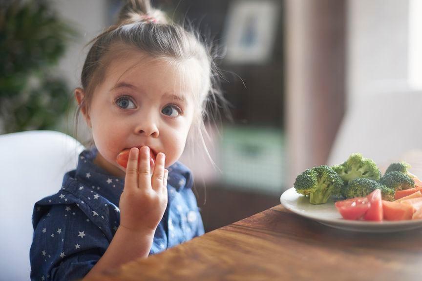 Mädchen knabbert an rohem Gemüse