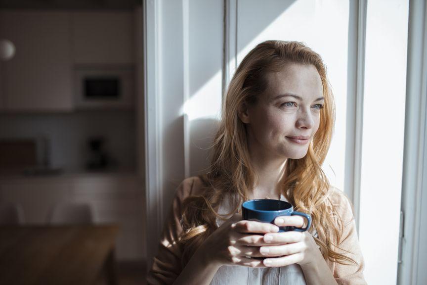 Frau am Fenster mit einer Tasse in der Hand