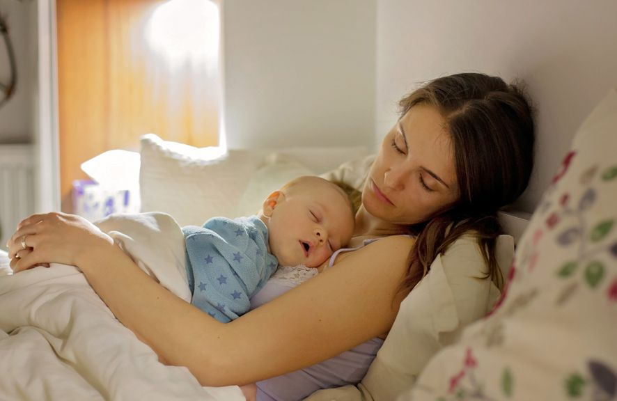 Mutter hält Baby im Arm, beide schlafen