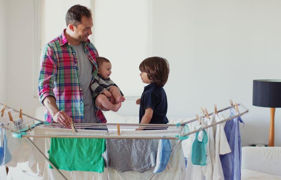 Vater mit seinen zwei Kindern beim Wäscheaufhängen