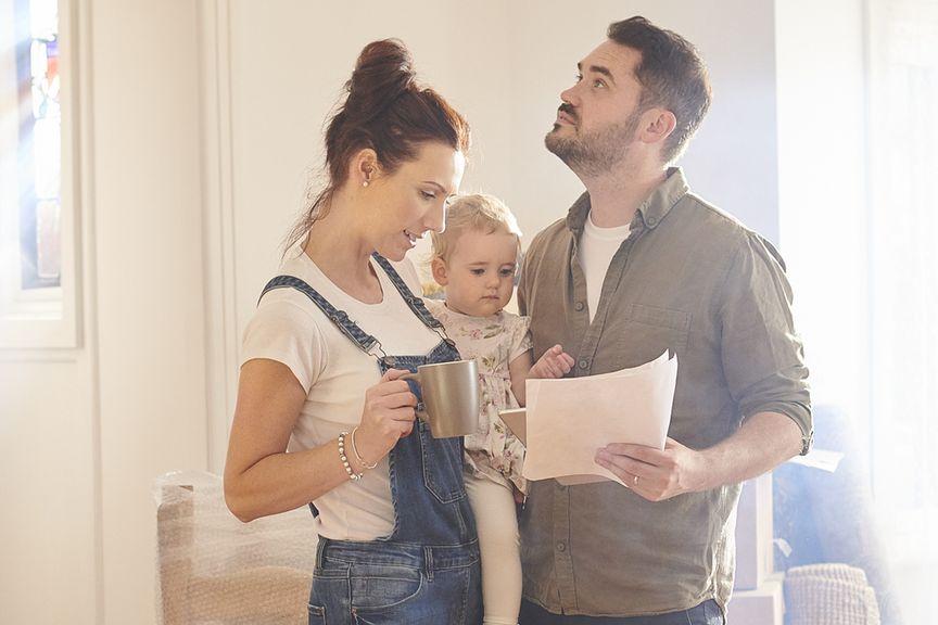 Paar mit Kind überprüft Formulare beim Umzug