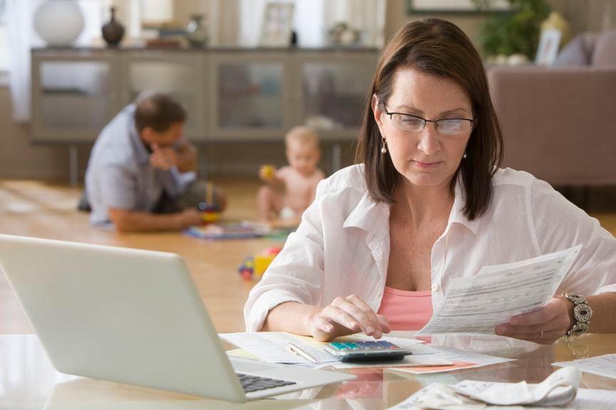 Frau bezahlt Rechnungen, Mann und Baby im Hintergrund