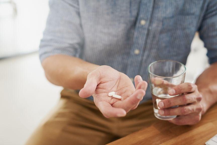 Mann mit Medikamenten und Wasserglas in der Hand