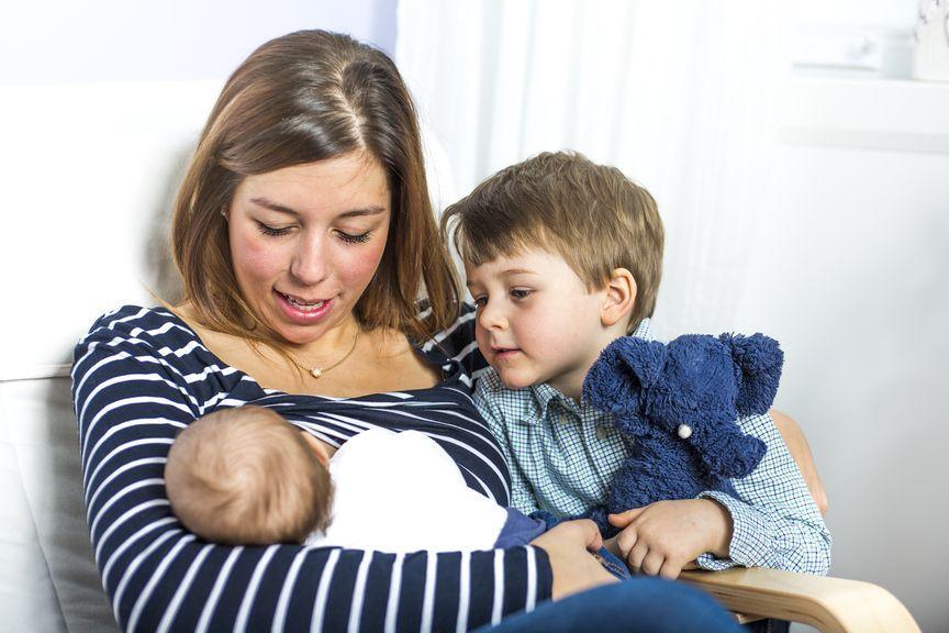 Mutter stillt ihr Neugeborenes, Geschwister schaut zu