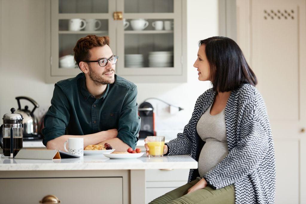 Werdende Eltern unterhalten sich am Küchentisch