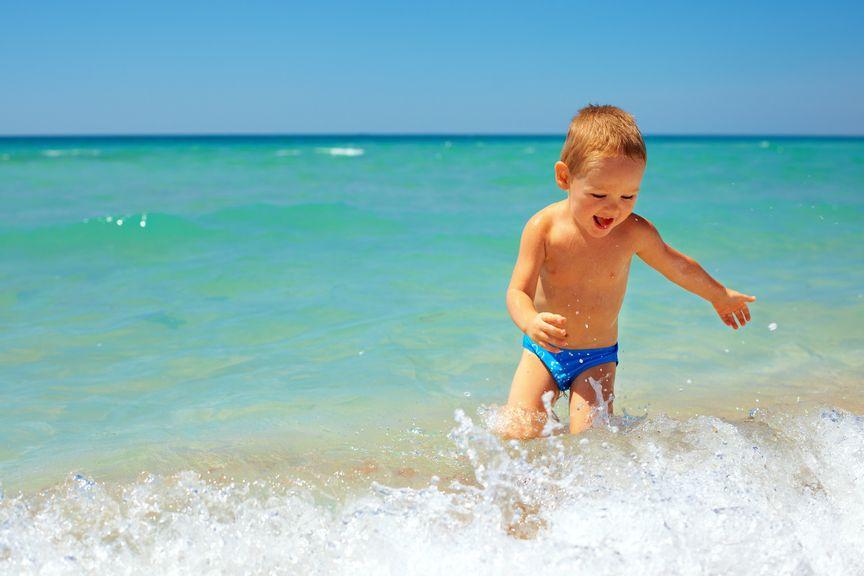 Kind planscht in den Wellen