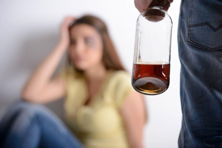 Mann mit Flasche in der Hand, Frau an der Wand sitzend