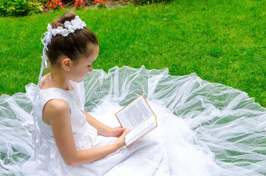 Mädchen in Kommunionskleid sitzt auf der Wiese