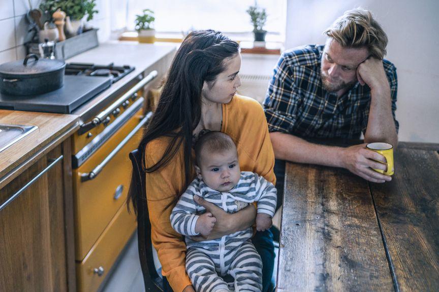 Paar mit Baby am Küchentisch